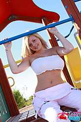 Tegan Brady Seated On Playground Equipment Arms Raised Big Breasts Filling Her Boob Tube