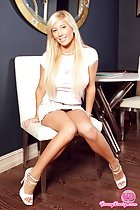 Blonde sitting on chair long hair short skirt knees pressed together in high heels