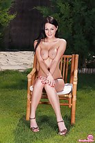 Seated topless on chair arms crossed squeezing big breasts together high heels