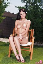 Dana I seated nude on chair outdoors arms crossed under her big tits nice legs wearing high heels