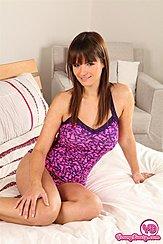 Sitting On Bed Wearing Purple Sleepwear Hand On Her Thigh
